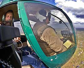 Ed Fink flying in Robinson R-44 helcopter